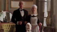 Medium shot portrait of butler and maid with toy poodle / maid holding dog's leash