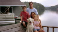 Medium shot portrait of family with pet Labrador retriever sitting on dock