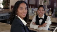 Medium shot portrait of hotel employees at bar smiling at camera