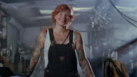 Medium shot portrait of smiling woman wearing overalls in workshop / arms covered with tattoos