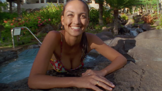 Medium shot portrait of woman leaning on edge of pool / smiling at camera