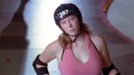 Medium shot portrait of woman wearing roller derby helmet / woman past skating in background