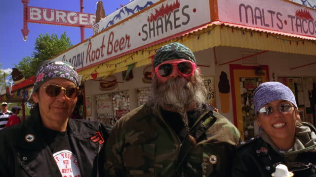 Medium shot portrait three male and female bikers in front of snack bar with one eating ice cream / Arizona