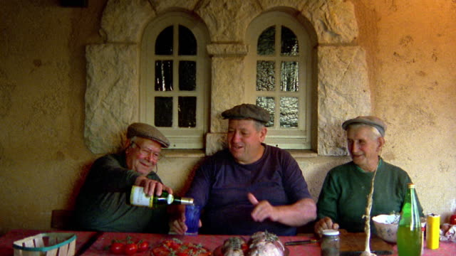 Medium shot portrait three senior men sitting at table drinking wine and waving / Provence, France