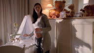 Medium shot pregnant woman decorating crib with mobile and teddy bear in nursery room