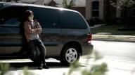Medium shot pre-teen boy leaning against minivan / teenage girls walking by