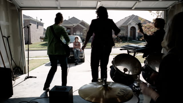 Medium shot pre-teen boy watching rock band of middle age women performing in garage