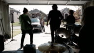 Medium shot pre-teen boy watching rock band of middle age women performing in garage / pre-teen boy closing garage door on them