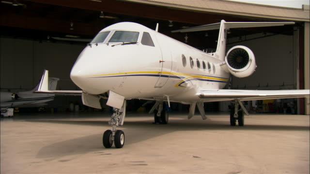 Medium shot Private jet outside hangar at airport / Long Beach, California, USA