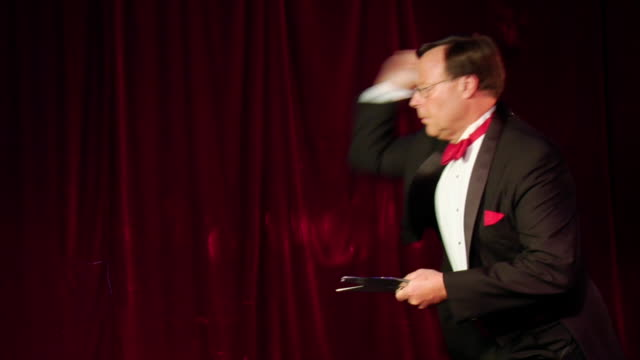 Medium shot profile of knife thrower throwing knives against red velvet curtain