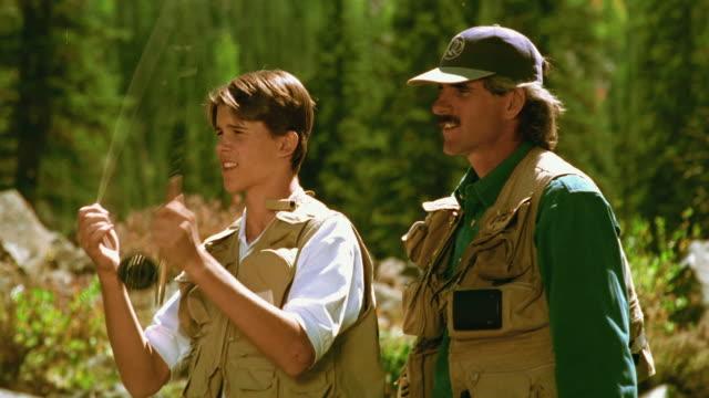 Medium shot profile older man teaching teenage boy fly fishing / Arizona