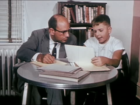 1955 medium shot Psychologist administering Rorschach test to boy and taking notes / AUDIO