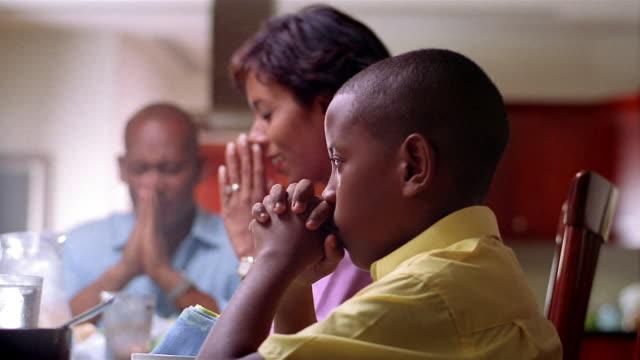Medium shot rack focus family praying before meal