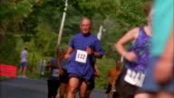 Medium shot rack focus people running in road race with person handing them cups of water from sidelines / Vermont
