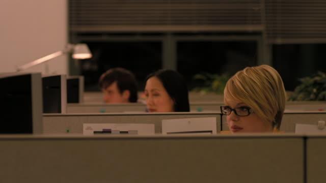 Medium shot rack focus three office workers talking in their cubicles