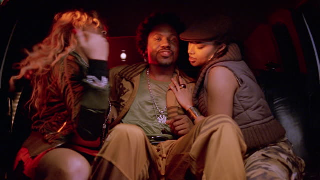 Medium shot rapper being fondled by two women in limo / threesome dancing to music