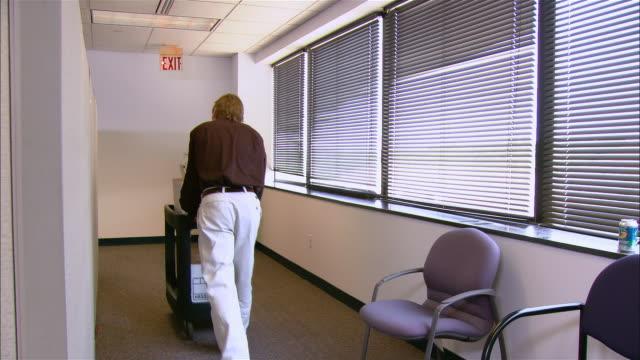 Medium shot rear view man pushing mail cart along corridor