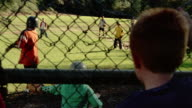Medium shot rear view of boy watching kids play baseball from behind fence / batter hits the ball