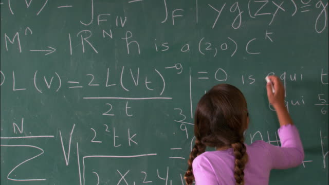 Medium shot rear view of girl figuring out math problem on chalkboard