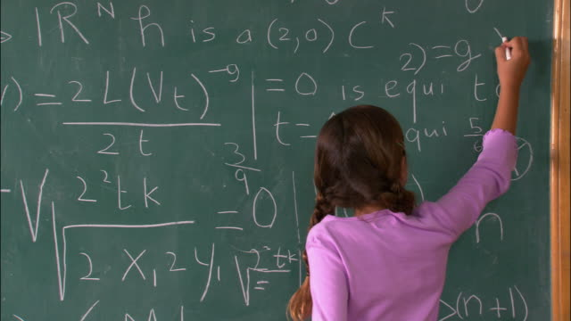 Medium shot rear view of girl figuring out math problem on chalkboard / turning around and looking satisfied