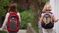 Medium shot rear view of two girls wearing backpacks walking down sidewalk / Glenwood Springs, Colorado