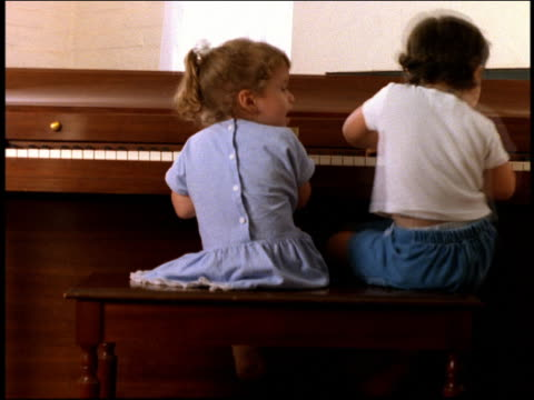 Medium shot rear view two toddlers sitting at piano with one shaking backside humorously