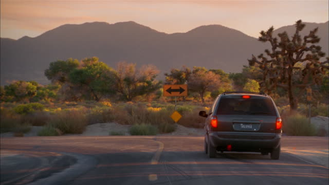 Medium shot rear view van approaching fork on desert road / deciding which turn to make / making right turn