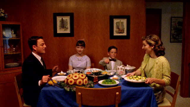 Medium shot REENACTMENT family passing food around dinner table