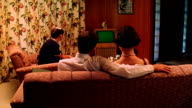 Medium shot REENACTMENT family watching TV in living room / TV screen is green for use of chroma key