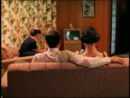 Medium shot REENACTMENT family watching TV in living room with parents on sofa in foreground