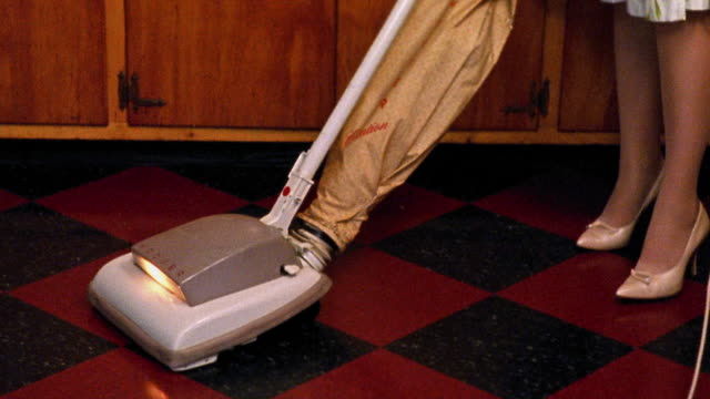 Medium shot REENACTMENT legs of woman as she vacuums linoleum floor in kitchen