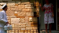 Medium shot REENACTMENT milkman delivering milk and handing bottle to woman at front door of house