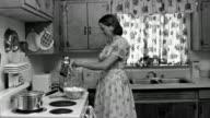 Medium shot REENACTMENT woman breaking eggs into mixer bowl in kitchen, then exiting