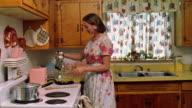 Medium shot REENACTMENT woman entering kitchen and turning on electric mixer