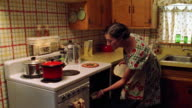Medium shot REENACTMENT woman removing roast from oven, holding roast and kicking leg back while smiling at cam in kitchen