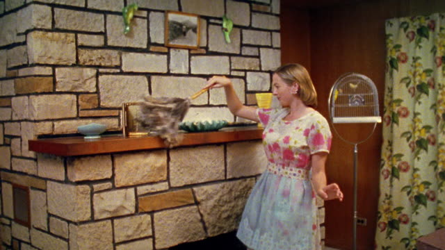 Medium shot REENACTMENT woman smiling and dusting fireplace mantle with feather duster