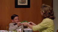 Medium shot REENACTMENT young boy passing bowl of gelatin to woman, who then passes it on at dinner table