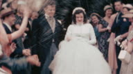 1951 medium shot rice being thrown on bride and groom leaving church / wedding guests in background