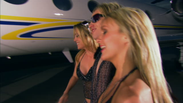 Medium shot Rock star entering private airplane with two groupies / Long Beach, California, USA
