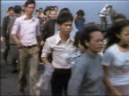 1975 medium shot Saigon evacuees walking quickly aboard a US carrier ship
