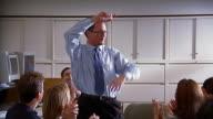 Medium shot sales manager dancing around / staff sitting around him laughing and applauding