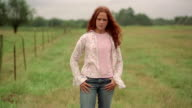 Medium shot selective focus zoom in portrait of girl standing in field smiling at CAM / crossing arms