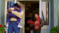Medium shot senior couple greeting young boy and girl on front porch + hugging them / Arizona