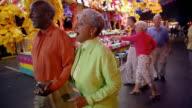 Medium shot senior couple holding hands and walking through amusement park