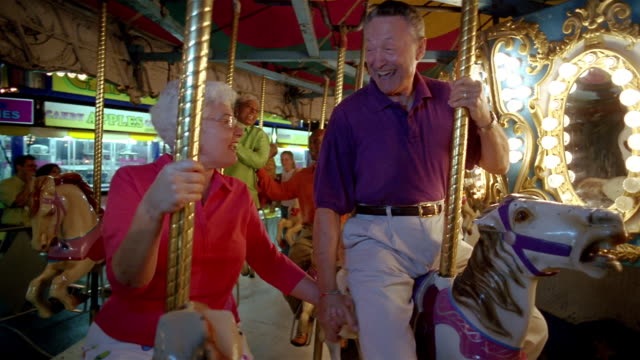 Medium shot senior couple holding hands on merry-go-round