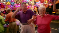 Medium shot senior couple winning prize at amusement park