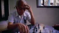 Medium shot senior Hispanic man playing chess / Cuba