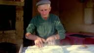 Medium shot senior man in hat kneading dough outdoors / Provence, France