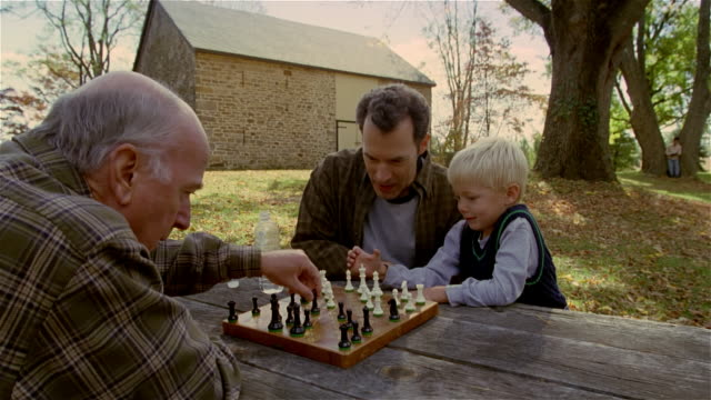 Medium shot senior man playing chess against mature man and young boy outdoors / autumn