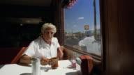 Medium shot senior man sitting in cafe, drinking coffee, and looking out window / Arizona